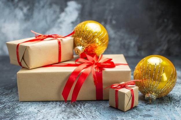 Vista frontale regali di natale legati con fiocchi rossi e giocattoli su foto di capodanno chiaro-scuro natale