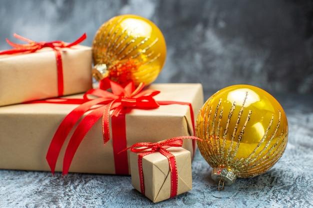 Vista frontale regali di natale legati con fiocchi rossi e giocattoli su foto chiaro-scuro regalo di capodanno vacanza colore natale