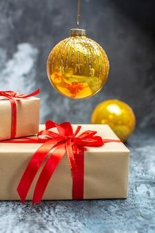 Vista frontale regali di natale legati con fiocchi rossi e giocattoli sulla foto chiaro-scuro regalo di natale di colore delle vacanze