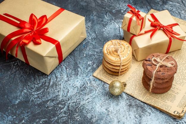 Vista frontale regali di natale con biscotti e giocattoli su un regalo di natale con foto a colori di capodanno chiaro-scuro