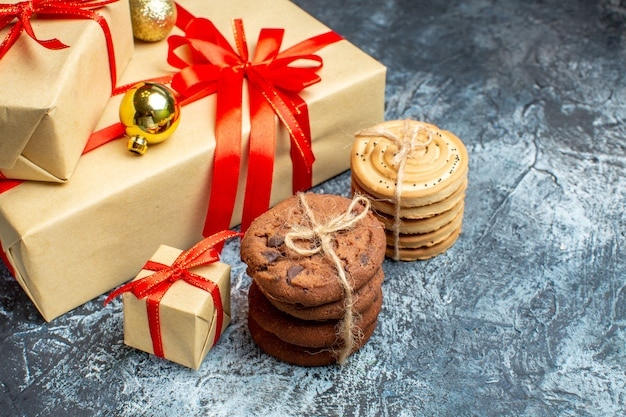 Front view xmas presents with sweet biscuits on light-dark holiday photo gift christmas color new year
