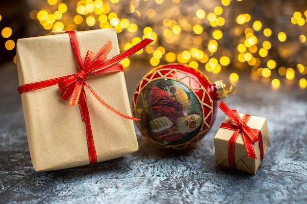 Вид спереди рождественские подарки с желтыми огнями на светло-темном фото рождество новый год цветной фейерверк