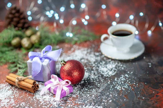 Vista frontale albero di natale palla piccoli regali polvere di cocco tazza di tè su sfondo scuro isolato