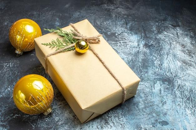 Vista frontale dell'albero di natale giocattoli con regalo su foto colore chiaro-scuro natale capodanno