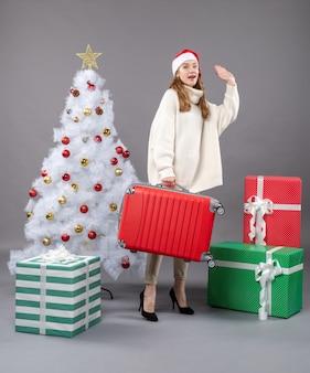 彼女の旅行バッグを保持し、さようならを言っている正面のクリスマスの女性