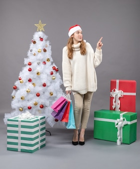 Front view xmas woman holding many colorful shopping bags