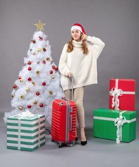 흰색 크리스마스 트리 근처에 서 전화 나 전화 기호를 보여주는 전면보기 크리스마스 여자