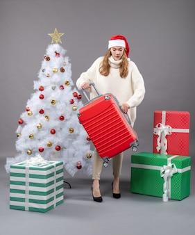 Вид спереди рождественская женщина в шляпе санта-клауса сидит возле рождественской елки