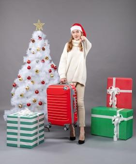 彼女の赤い旅行バッグを保持しているサンタの帽子と正面のクリスマスの女性