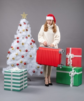 彼女の旅行バッグを保持しているサンタの帽子と正面のクリスマスの女性