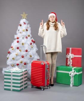 赤いクリスマスのおもちゃで白いクリスマスツリーの近くに幸運のサインを作るサンタ帽子と正面のクリスマスの女性