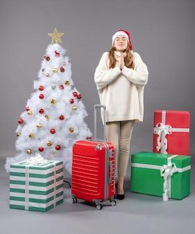 赤いクリスマスのおもちゃで白いクリスマスツリーの近くで願い事をするサンタの帽子をかぶった正面図のクリスマスの女性