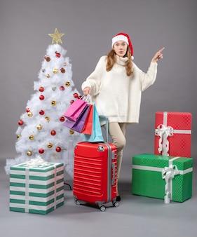 正面図クリスマスツリーギフトボックスの近くに立っているサンタ帽子を持つクリスマスの女性