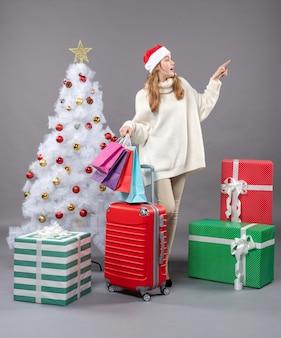 Вид спереди рождественская женщина в шляпе санта-клауса, стоящая возле рождественской елки