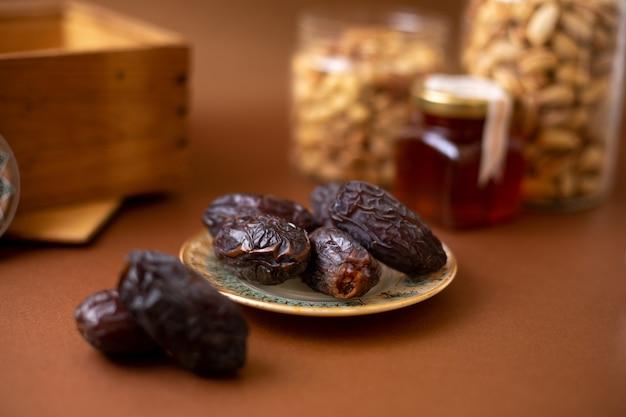 Вид спереди xurma коричневый вкуснятина вся внутренняя тарелка на деревянной коричневой поверхности