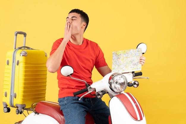 原付の地図を保持しているハンサムな男をあくびする正面図