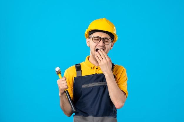 Vista frontale del lavoratore maschio che sbadiglia in uniforme gialla su un blu