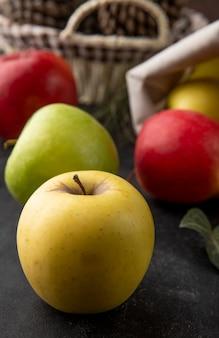 Mela gialla di vista frontale con la mela rossa e verde su una tabella nera