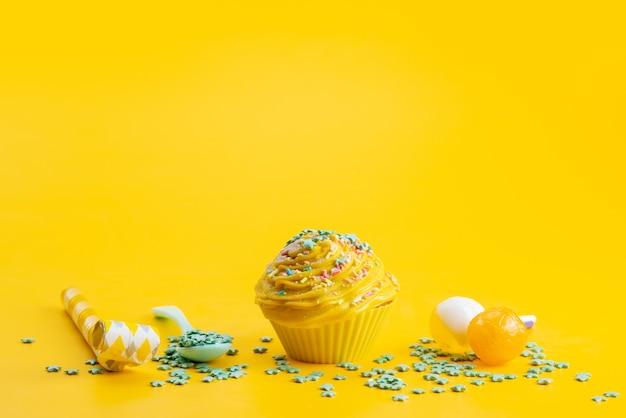Una torta gialla vista frontale deliziosa e gustosa insieme a caramelle a forma di stella verde sullo scrittorio giallo, torta color zucchero dolce