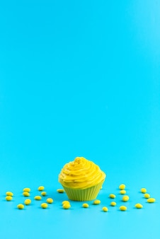 A front view yellow cake with candies on blue