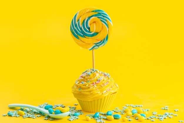 A front view yellow cake with lollipop on top along with colored candies on yellow