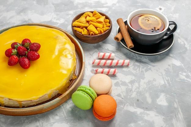 Torta gialla vista frontale con macarons e tazza di tè sulla superficie bianca