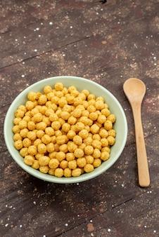 暗い木、朝食コーンフレークシリアル食品のプレート内の正面黄色の穀物
