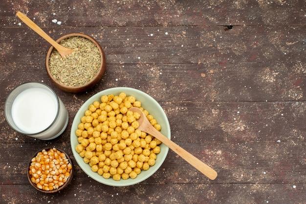 Cereali gialli di vista frontale dentro il piatto con latte freddo fresco sul pasto scuro dei cereali dei fiocchi di granturco della prima colazione