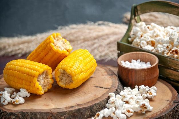Vista frontale calli gialli affettati con popcorn sull'olio dell'albero delle piante di snack di mais superficie scura