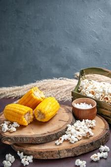 Вид спереди желтые зерна, нарезанные попкорном на темном столе, кукурузные закуски, масло дерева