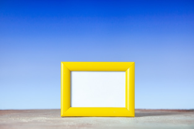 Front view of yellow empty picture frame standing on table on white and blue surface with free space