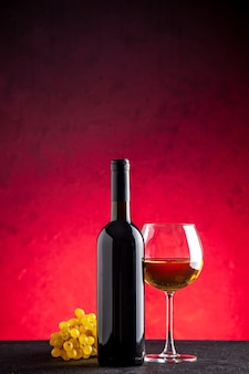 Вид спереди желтый виноград, бутылка вина, вино в стекле на красном фоне
