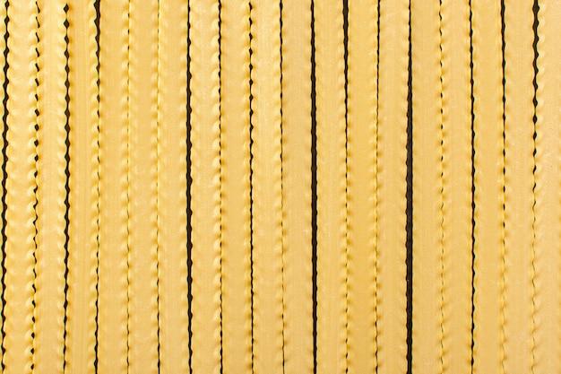 Una pasta lunga gialla di vista frontale ha formato il pasto italiano crudo dell'alimento della pasta crudo