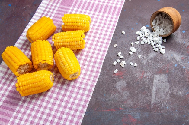 Front view yellow sliced corns raw and fresh on the dark surface corn plant food raw fresh