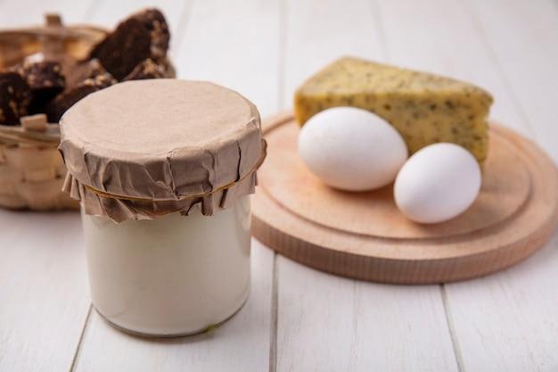 白い背景の上のスタンドにチーズと鶏卵と瓶の中の正面図ヨーグルト