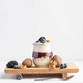 Front view yogurt with jam and fruits on board