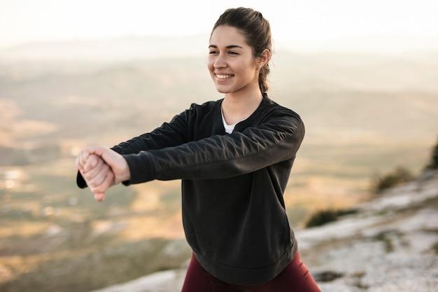 Вид спереди молодой и улыбающейся женщины тренируется
