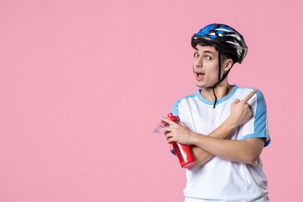 Вид спереди молодой спортсмен в спортивной одежде шлем и держит бутылку воды