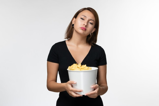 Giovane femmina attraente di vista frontale in canestro nero della tenuta della camicia con le patatine fritte sulla superficie bianca