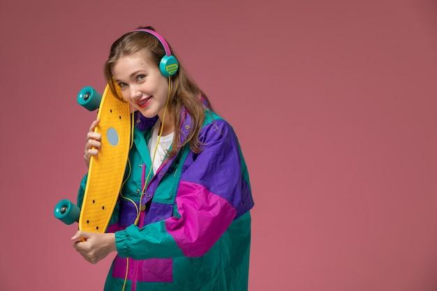 Вид спереди молодая привлекательная женщина в цветном пальто, держащая скейтборд с улыбкой на розовой стене, цвет модели женщина молодая девушка