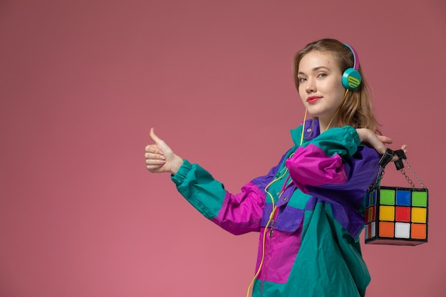 Giovane femmina attraente di vista frontale in cappotto colorato che ascolta la musica sulla ragazza della femmina di colore del modello della parete rosa scuro