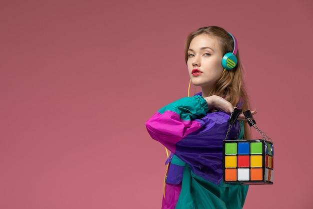 Giovane femmina attraente di vista frontale in cappotto colorato che ascolta la musica che tiene la borsa divertente sulla ragazza della femmina di colore del modello della parete rosa scuro