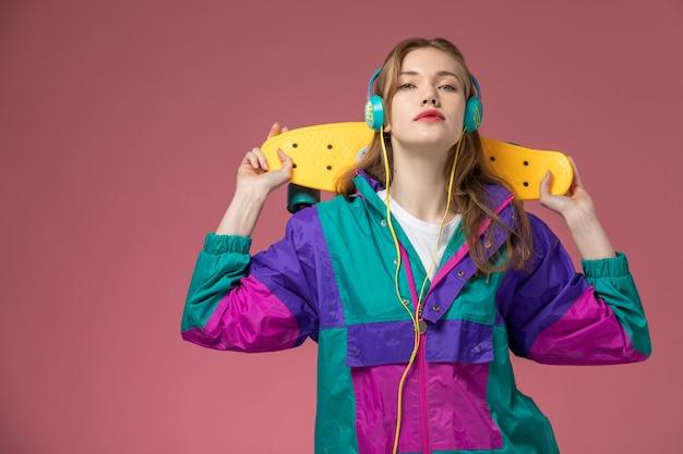Vista frontale giovane femmina attraente in cappotto colorato ascoltando musica e tenendo lo skateboard e ascoltando musica sul muro rosa modello colore femmina giovane