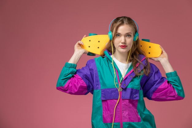 Front view young attractive female in colored coat listening to music holding skateboard on pink wall model female young