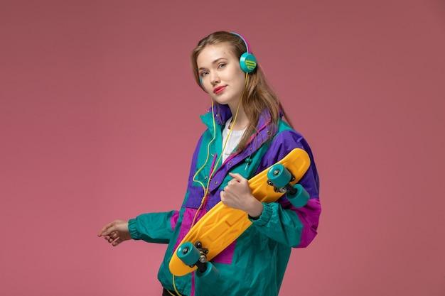 Giovane femmina attraente di vista frontale in cappotto colorato che ascolta la musica con lo skateboard sulla ragazza di colore rosa del modello della parete femminile