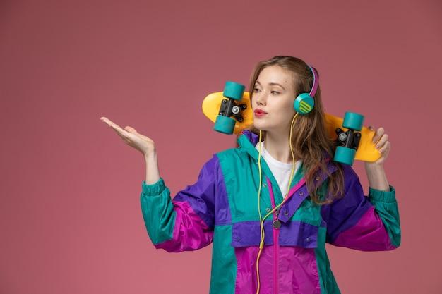 Vista frontale giovane femmina attraente in cappotto colorato in posa e ascolto di musica sul muro rosa modello colore femmina giovane