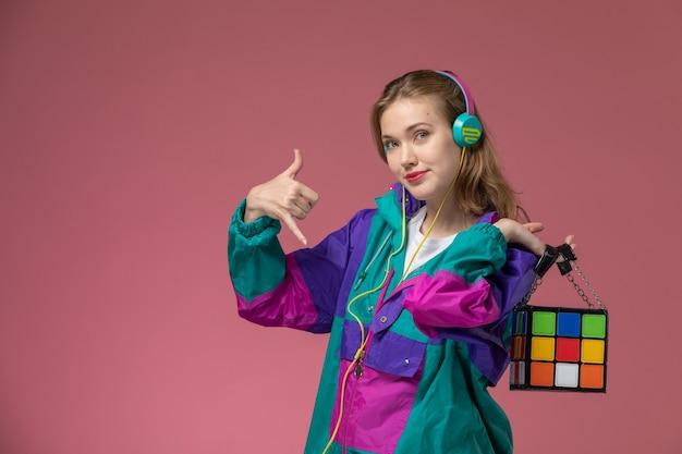 Vista frontale giovane femmina attraente in cappotto colorato sorridente ascoltando la musica sulla ragazza rosa modello scrivania colore femminile giovane