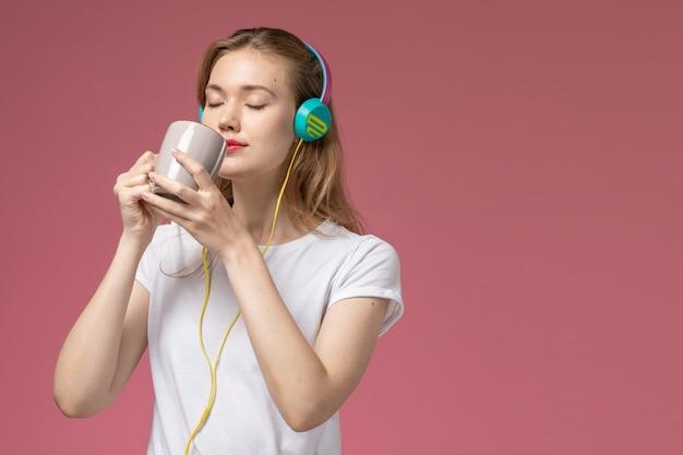 正面図若い魅力的な女性がお茶を飲み、ピンクの壁のモデルの色の女性の若いで音楽を聴いています