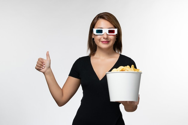 Front view young attractive female holding basket with potato cips in d sunglasses smiling on white surface