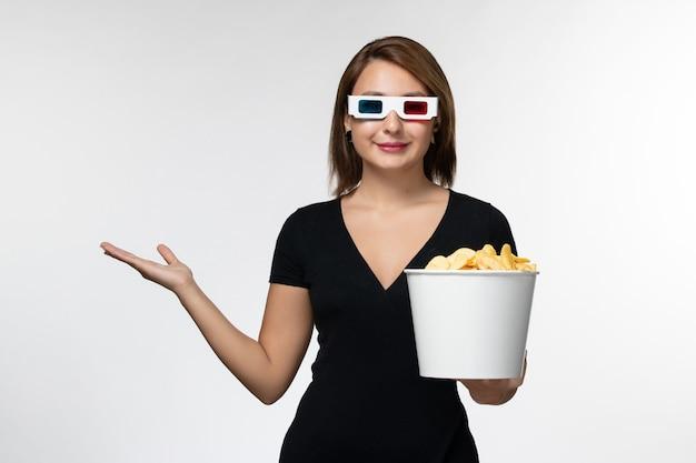 正面図明るい白い表面にdサングラスでジャガイモcipsとバスケットを保持している若い魅力的な女性